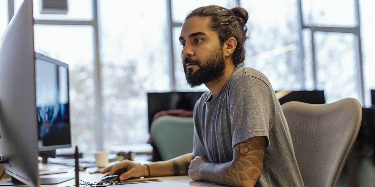 Portrait of Stylish Hipster Guy with Tattoo on Hand, Writes Notes in Computer at Office