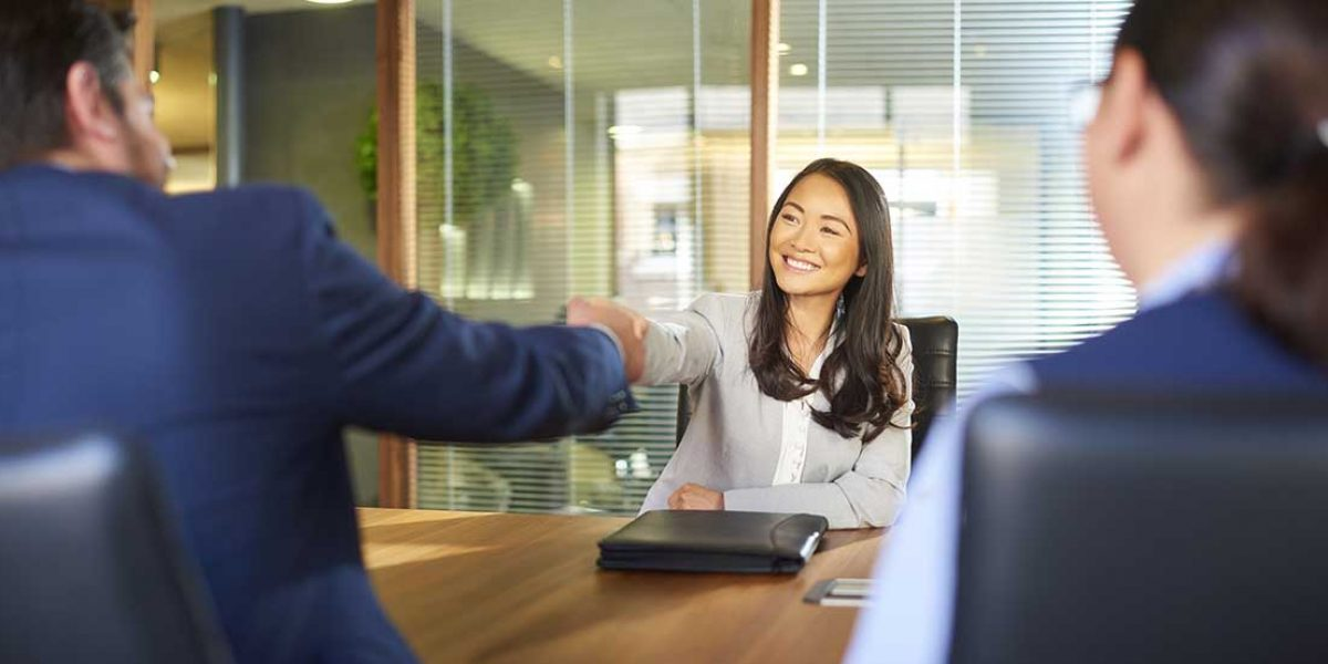 a young woman sits opposite the recruitment manager and shakes his hand as she gets the job