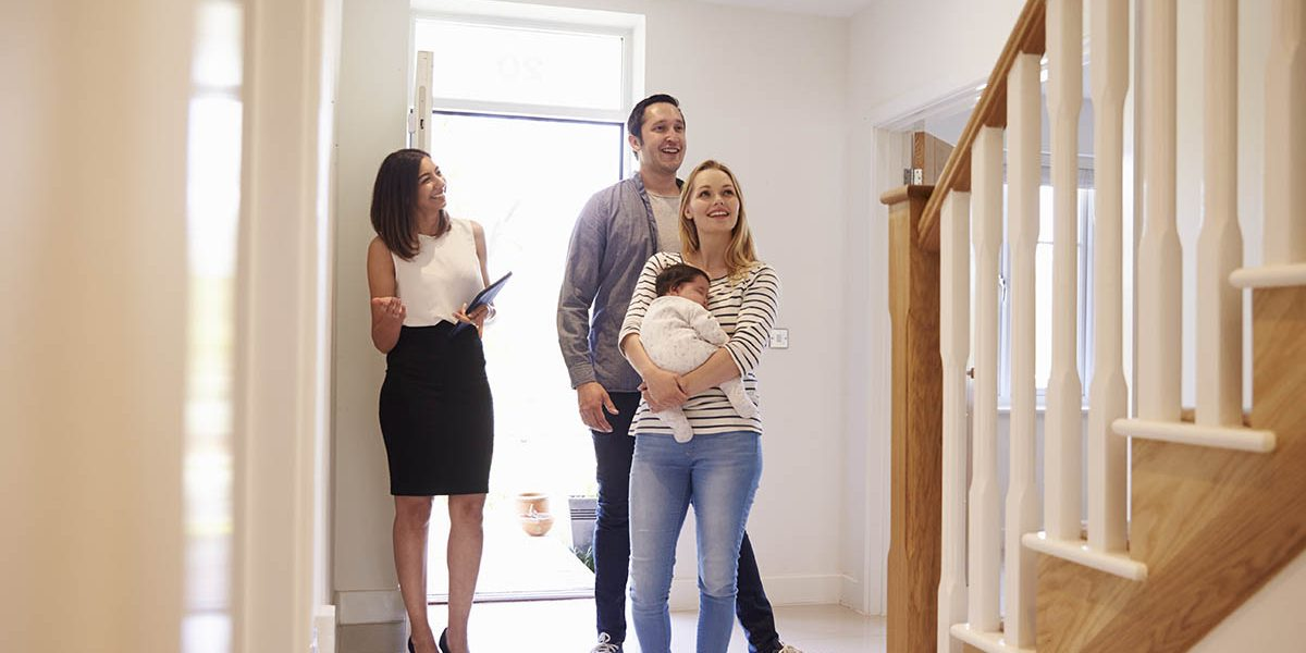 Realtor Showing Young Family Around Property For Sale