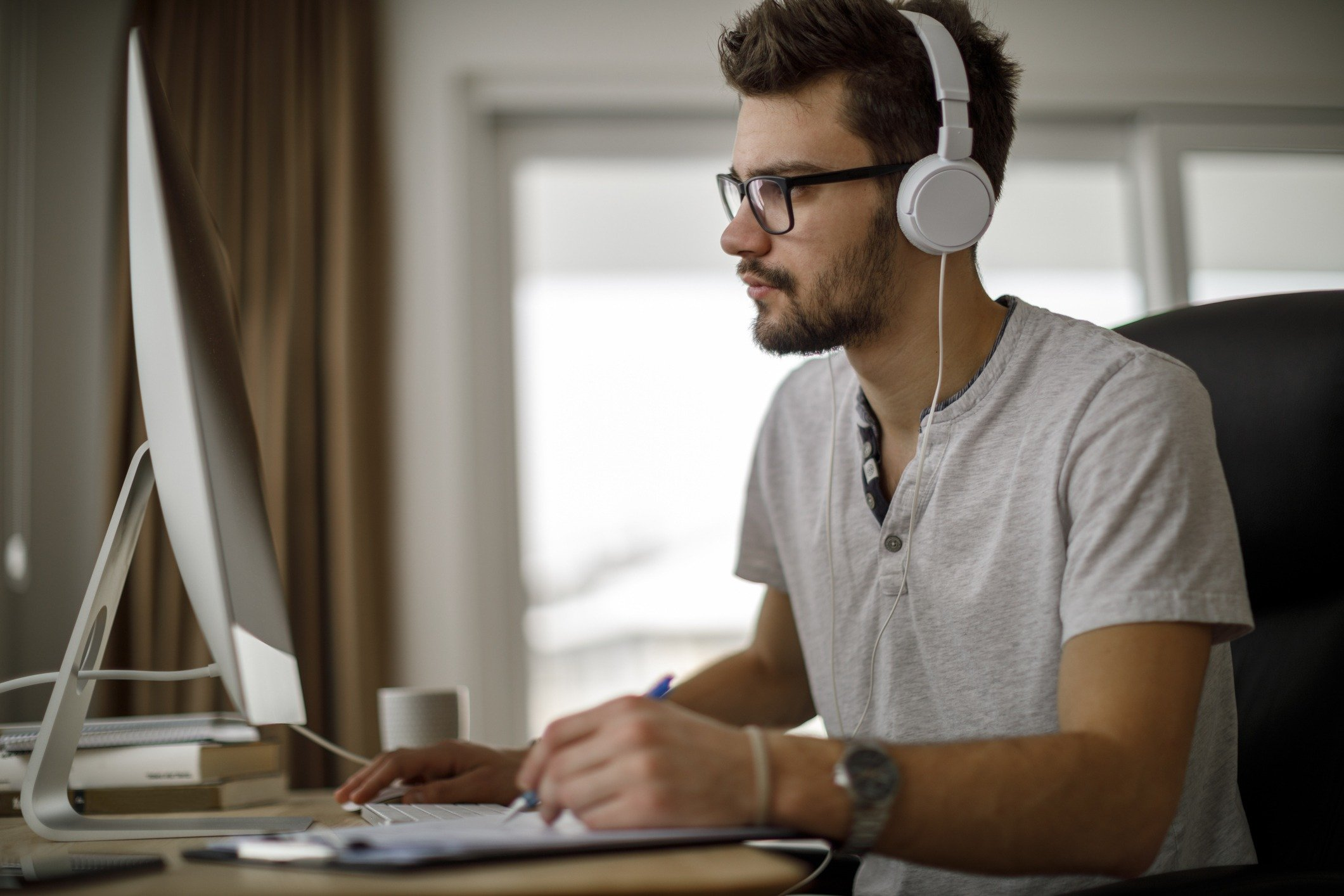 Young man using computer and taking notes - Featured Image