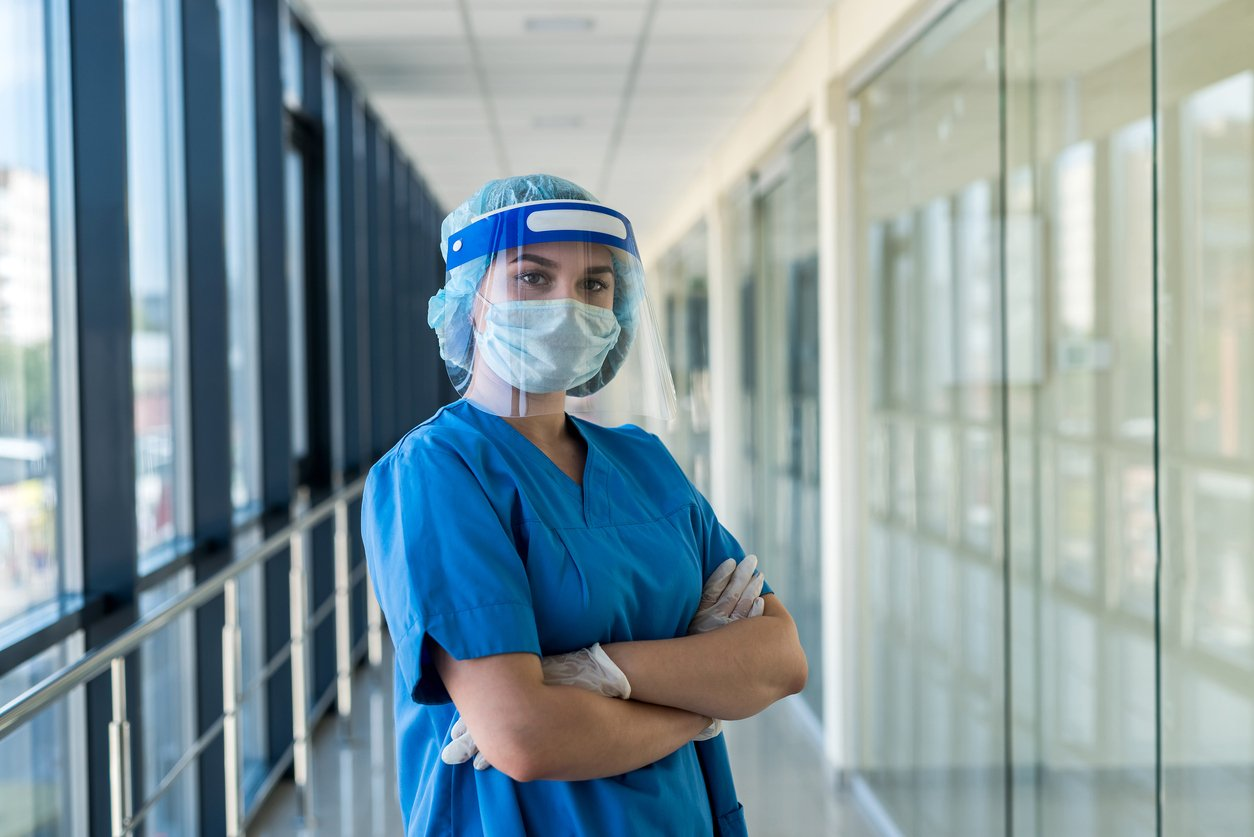 young nurse in blue uniform and protective shield to protect against a new dangerous virus covid19